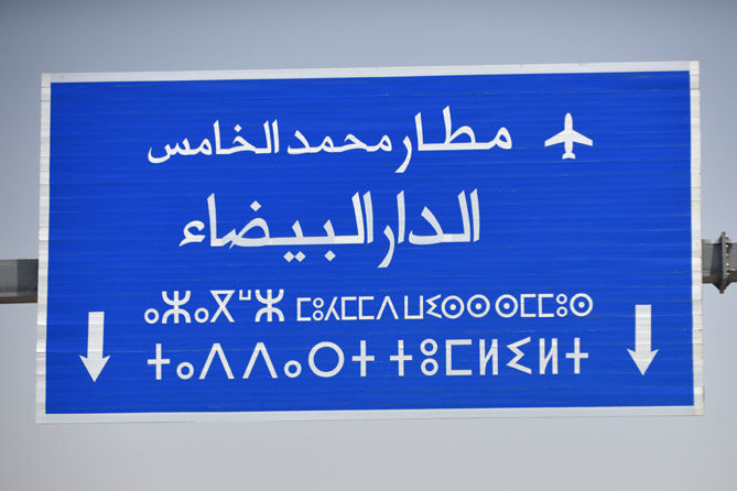 road sign with two alphabets—Arabic, and Tifinagh, used to write the Berber language