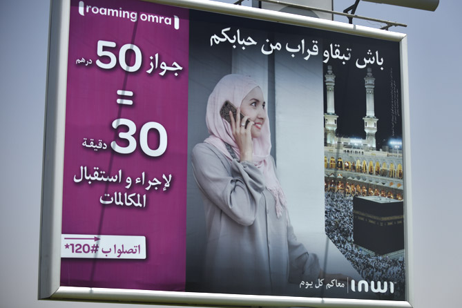 billboard with a picture of a woman in a hijab making a mobile call with Mecca as a backdrop